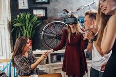 Moça entusiasmado que testa auriculares da realidade virtual quando seus amigos que olham, rindo e apoiando a Grupo de fotografia de stock