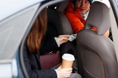 A moça envia o motorista no dinheiro alaranjado do revestimento para o curso Fotos de Stock