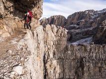 A moça escala através da elevação do ferrata nas montanhas Foto de Stock
