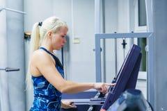 A moça escolhe correr na escada rolante no gym fotografia de stock