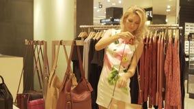 A moça escolhe e tenta sobre bolsas em uma loja de roupa video estoque