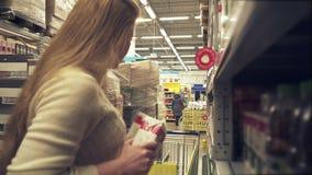 A moça escolhe o suco no vídeo da metragem do estoque do supermercado vídeos de arquivo