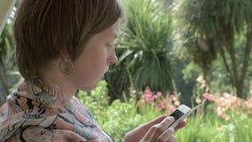 A moça escreve uma mensagem no telefone no jardim tropical - Geórgia video estoque