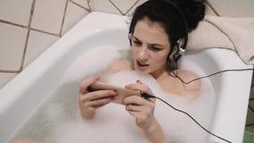 A moça escuta a música com fones de ouvido de um smartphone impermeável e o canto em um banho de espuma filme