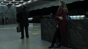 A moça escuta a música nos fones de ouvido no túnel do metro Estudante fêmea novo que escuta a música em grande video estoque