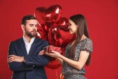 A moça está apresentando um presente e balões a seu homem considerável ressentido fotos de stock royalty free