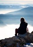 A moça está descansando na parte superior da montanha Fotografia de Stock Royalty Free