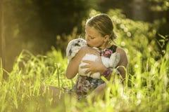 A moça está guardando o coelho branco foto de stock royalty free