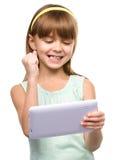 A moça está jogando o jogo usando a tabuleta imagem de stock