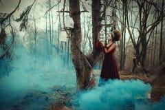 A moça está levantando em um vestido vermelho com penteado criativo foto de stock