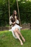 A moça está montando o balanço da corda no estilo dos povos da floresta Fotos de Stock Royalty Free