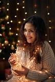 A moça está nas luzes e na decoração de Natal, vestidas em branco, árvore de abeto no fundo de madeira escuro, conceito do feriad foto de stock royalty free