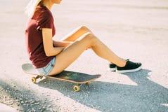 A moça está sentando-se em um skate, uma tatuagem em seu pé imagem de stock royalty free