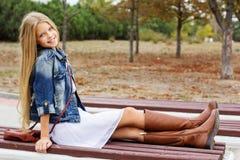 A moça está sentando-se no banco Imagens de Stock Royalty Free