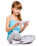 A moça está usando a tabuleta fotografia de stock