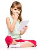 A moça está usando a tabuleta ao sentar-se no assoalho foto de stock royalty free