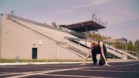Moça, físico desportivo, no estádio Vai à linha do começo, obtém em um baixo começo, e na corrida dos começos vídeos de arquivo
