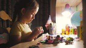 A moça faz seus trabalhos de casa na tabela sob a luz de uma lâmpada passatempo criativo da princesa pequena estilo de vida de filme