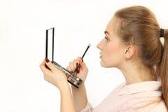 A moça faz uma composição na frente de um espelho cosmético pequeno Fotografia de Stock Royalty Free