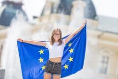 Moça feliz bonito com a bandeira da União Europeia na frente de uma construção histórica em algum lugar em Europa fotografia de stock
