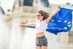 Moça feliz bonito com a bandeira da União Europeia na frente de uma construção histórica em algum lugar em Europa imagens de stock royalty free