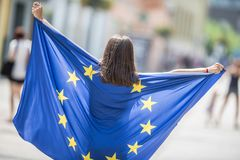 Moça feliz bonito com a bandeira da União Europeia nas ruas em algum lugar em Europa imagens de stock