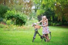 Moça feliz com bicicleta e flores Foto de Stock Royalty Free