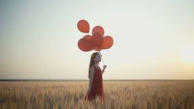 Moça feliz com os balões que correm no campo de trigo no por do sol vídeo 4K video estoque