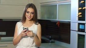Moça feliz com um telefone em suas mãos que dançam na cozinha em casa vídeos de arquivo