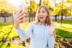 A moça feliz com um telefone, toma imagens dsi mesma, no fotografia de stock royalty free