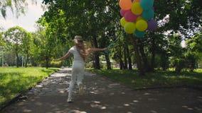 A moça feliz corre no parque ensolarado verde e guarda balões coloridos filme