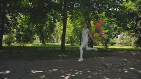 A moça feliz corre no parque ensolarado verde e guarda balões coloridos vídeos de arquivo