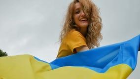 Moça feliz de riso com a bandeira ucraniana azul e amarela em suas mãos sobre o fundo do céu filme