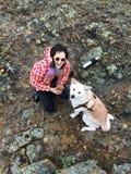 Moça feliz de sorriso com a caneca esmaltada com chá nas mãos e inu bonito esperto de akita do japonês do cão em uma costa rochos Foto de Stock Royalty Free