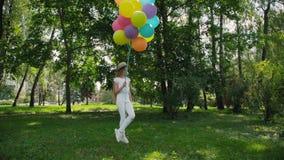 A moça feliz levanta no parque ensolarado verde e guarda balões coloridos video estoque