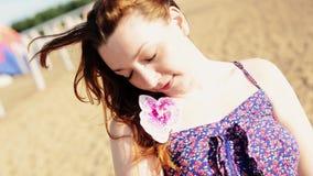 A moça feliz na praia com flor sorri in camera ensolarado carefree dança filme