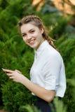 Moça feliz no parque com o telefone nas mãos fotografia de stock