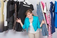 A moça feliz olhou acima da roupa que pendura em ganchos foto de stock royalty free