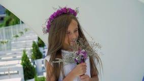 Moça feliz que aspira flores nas mãos e que sorri na barra de baía lentamente filme