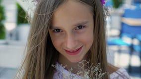 Moça feliz que aspira flores nas mãos e que sorri na barra de baía lentamente video estoque