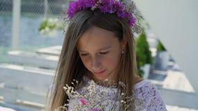 Moça feliz que aspira flores nas mãos e que sorri na barra de baía lentamente vídeos de arquivo