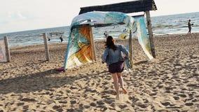 Moça feliz que corre na praia Sorriso na câmera Decole o revestimento Árvore no campo filme