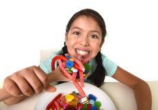 Moça feliz que guarda a colher que come do prato completamente do pirulito dos doces e de coisas açucarados Imagem de Stock Royalty Free