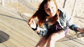A moça feliz senta-se na rede no sorriso da praia in camera Dia ensolarado férias vídeos de arquivo