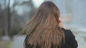 Moça glamoroso elegante com o cabelo longo que veste caminhadas e a pose pretas do revestimento na câmera Estilo da moda da forma filme
