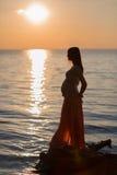 Moça grávida na praia no por do sol na praia Imagem de Stock