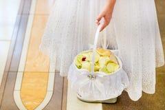A moça guarda uma cesta das pétalas Fotos de Stock Royalty Free