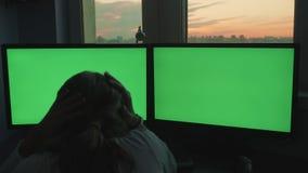 A moça infeliz agarra sua cabeça na frente de dois monitores grandes vídeos de arquivo