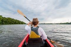 Moça irreconhecível que kayaking em um rio ou em um lago Menina feliz que canoeing em um dia de verão imagem de stock royalty free