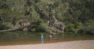 A moça joga em um rio seixoso rochoso raso como caminhadas do menino abaixo do riverbank video estoque